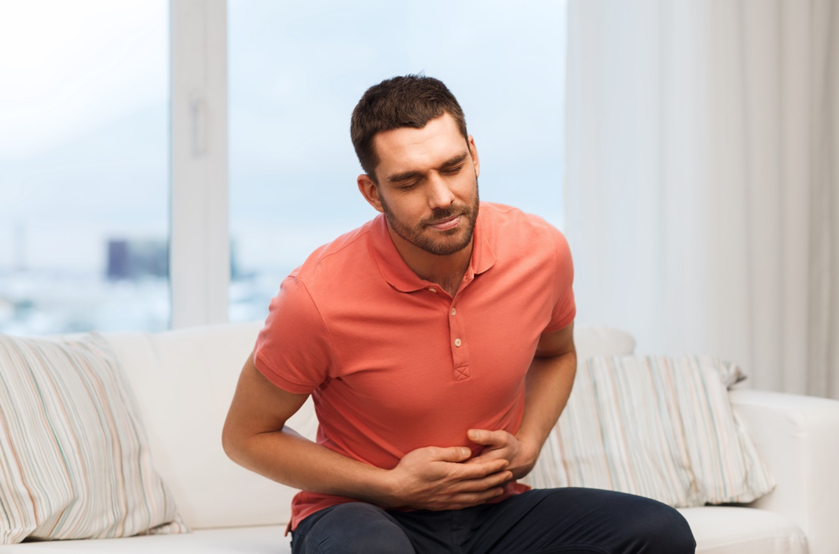 Unhappy Man Suffering From Stomach Ache At Home
